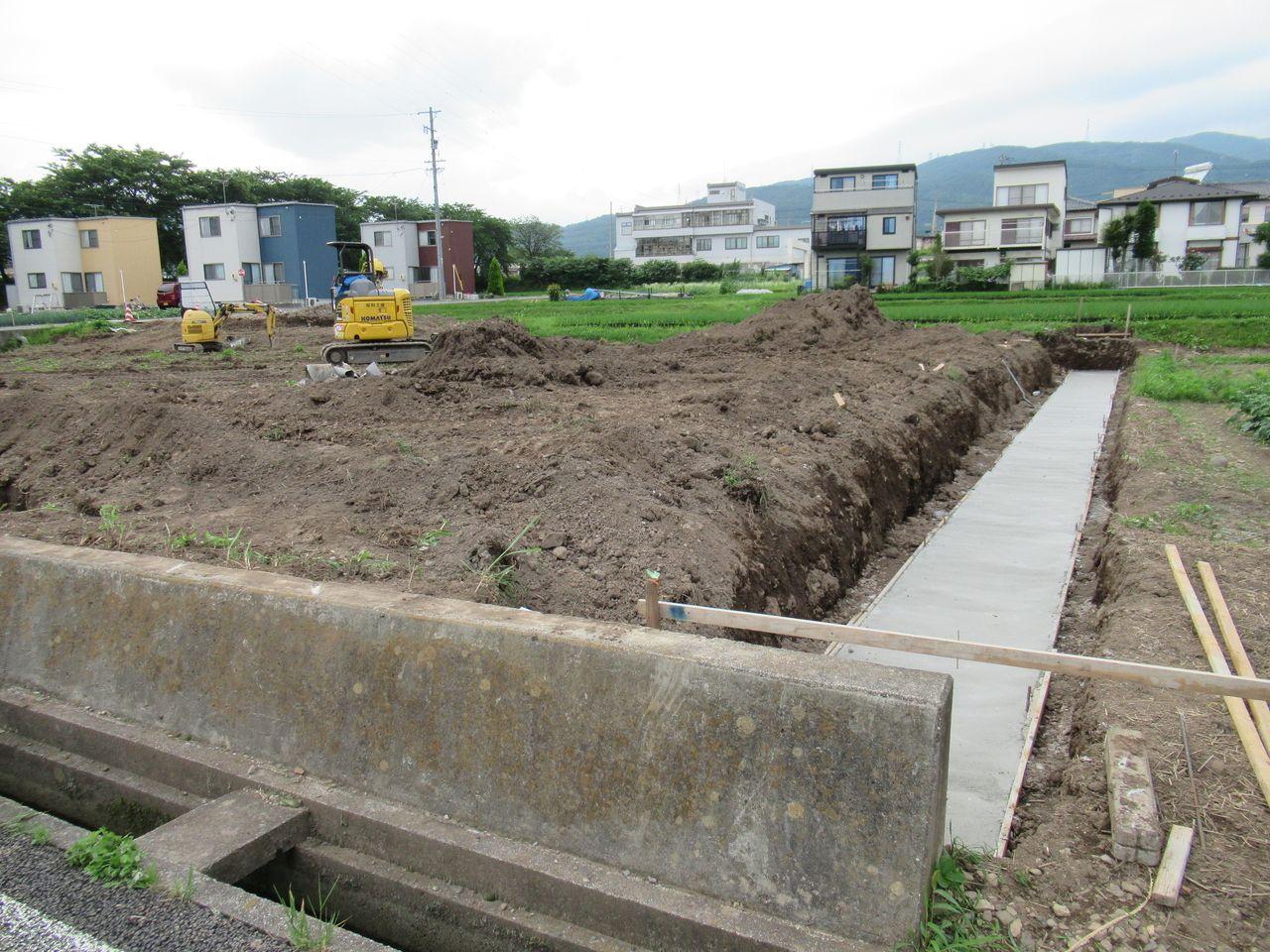 手前に見えるコンクリートの土留めは岡谷市所有の構造物です。出入口となる4m分しか壊すことが出来ないのでここは残します。 東隣とのコンクリート擁壁は、北側の田んぼの土地から、この市有構造物までの間に設置して、境界トラブルの起きないようしっかりと作ります。