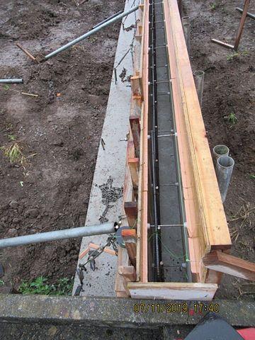 内側と外側に型枠が立てられて、中には鉄筋も組み終わっています。 次はコンクリートを流し込みます。打設する高さの目印としての役目や、完成時に面(角)取りが出来るように面木(役物)が取り付けられています。
